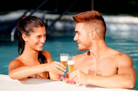 Happy couple relaxing in the pool in the summer celebrating their anniversary with champagne photo
