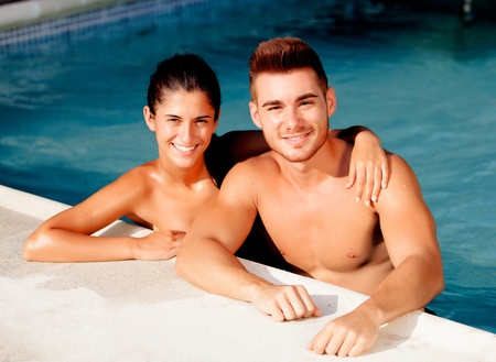 Happy couple relaxing in the pool in the summer photo