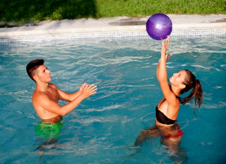 Happy couple relaxing in the pool in the summer playing with a ball photo