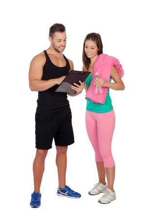 instrucciones: Entrenador personal guapo con una chica atractiva aislados en un fondo blanco Foto de archivo