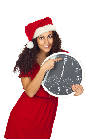 Pretty girl with christmas hat and a clock with twelve oclock photo