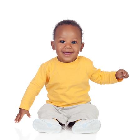 바닥에 앉아 사랑스러운 아프리카 아기는 흰색 배경에 고립