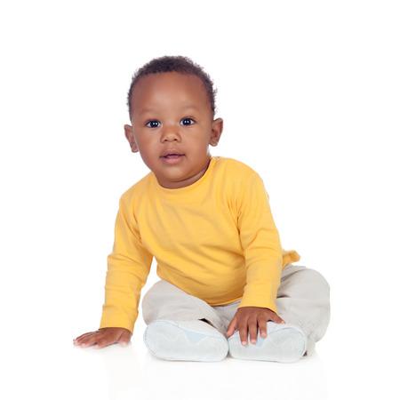 Aanbiddelijke Afrikaanse baby zittend op de vloer geïsoleerd op een witte achtergrond Stockfoto