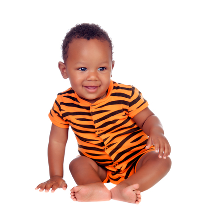 Adorable african baby with with brindle pajamas sitting on the floor isolated on a white background Stock Photo - 22513044