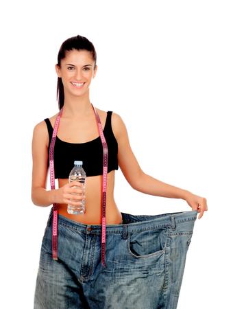 Slim donna torna con enormi pantaloni e una bottiglia d'acqua isolati su sfondo bianco
