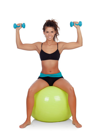 Attractive girl lifting dumbbells sitting on a ball isolated on a white background photo