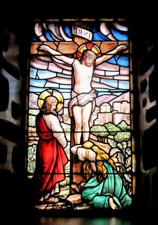 십자가에 못 박힌 예수와 마리아의 이미지와 다채로운 창 울고