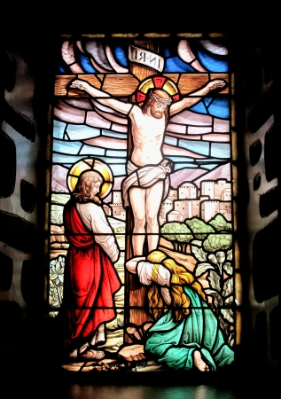 Colorful window with the image of the crucified Jesus and Mary crying