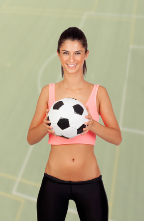 Brunette woman with a ball on a soccer field of background photo