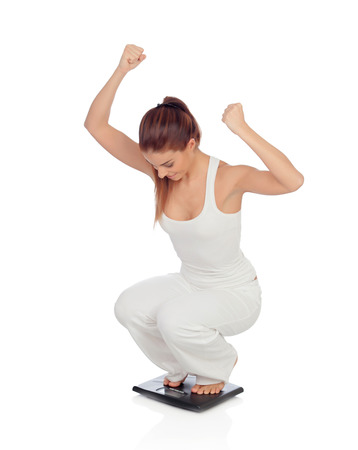 Pretty woman on seeing his new weight scale isolated on a white background photo