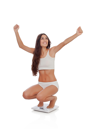 Happy woman celebrating her new weight on a scale isolated on a white background photo