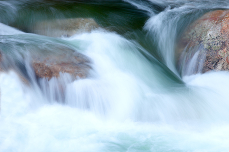 Nice creek with clear water flowing between the rocks photo