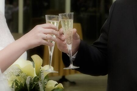 Hands of engaged couple toasting at their wedding day photo