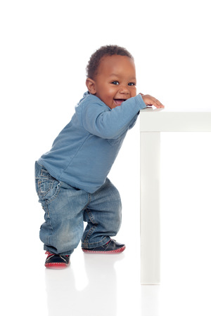 Beautiful african baby standig with a table isolated on a white background Archivio Fotografico
