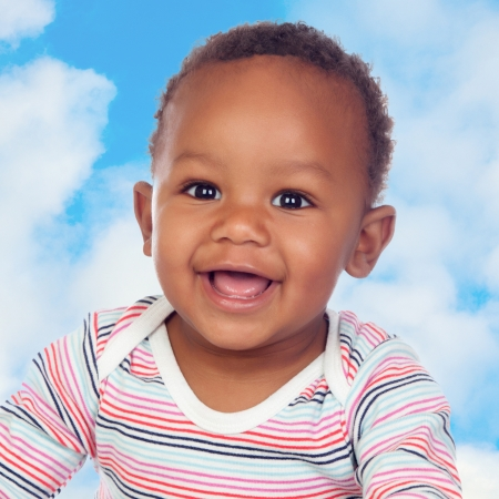 african american infant: Adorable african baby smiling with a blue sky of background