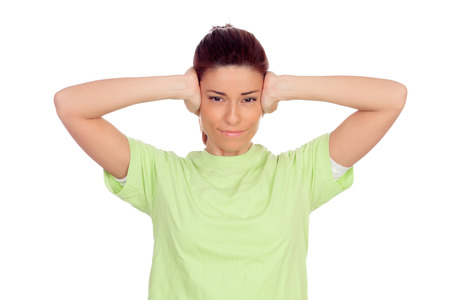 Nervous woman covering her ears isolated on a white background photo