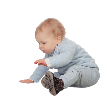 Adorable blonde baby sit on the floor isolated on a white background photo