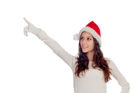 Attractive casual girl with Christmas hat pointing something isolated on a white background photo