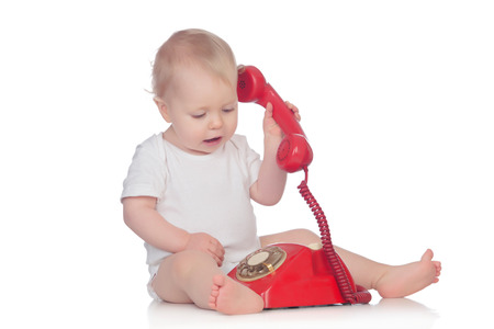 Cute caucasian baby playing with telephone isolated on a white background photo