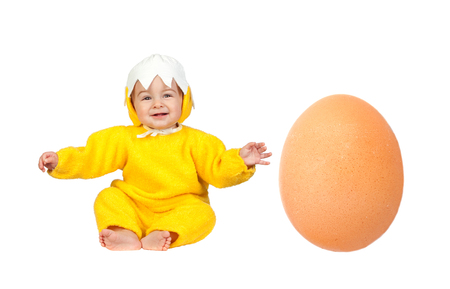 Nice baby chick disguised with a big egg at his side isolated on a white background Stock Photo - 25511188