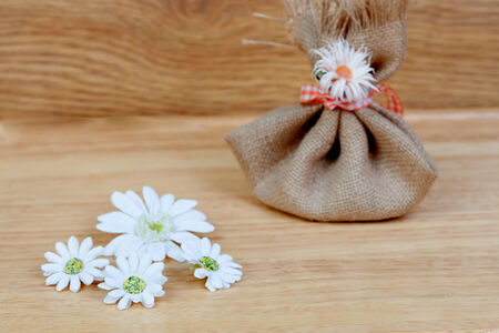 closed ribbon: Brown bag closed with a ribbon and flowers on a wooden  Stock Photo