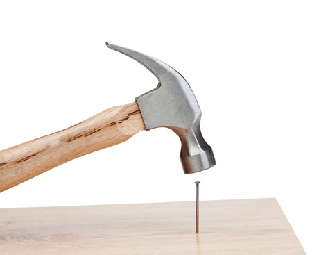 Hammer hitting a nail into a wood isolated on white background