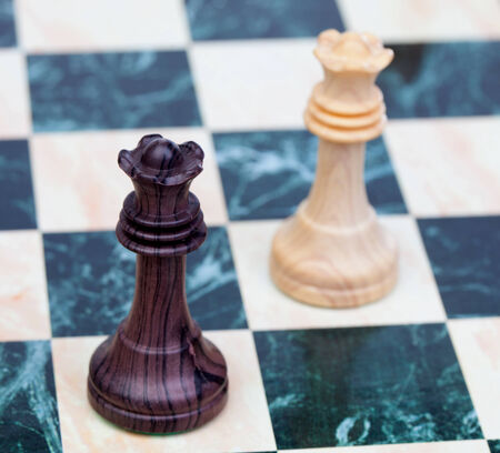 two faced: Two faced queens Wooden chess pieces on chessboard Stock Photo