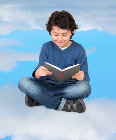 Adorable child reading sitting on the clouds photo