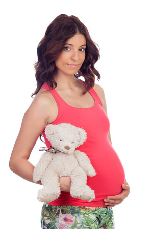Pregnant woman with a teddy isolated on a white background Stock Photo