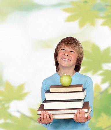 Funny child with many books and leaves of background. photo