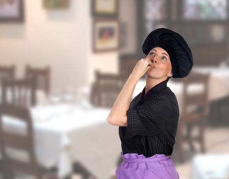 Woman making the gesture cook delicious in the restaurant photo
