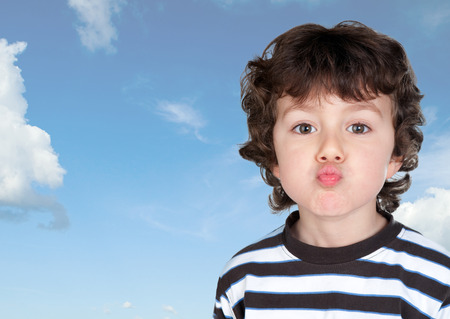 Funny child making grimace throwing a kiss with a blue sky background Stock Photo