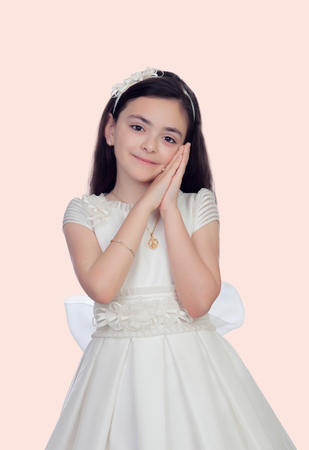Adorable little girl dressed in communion isolated on white background photo