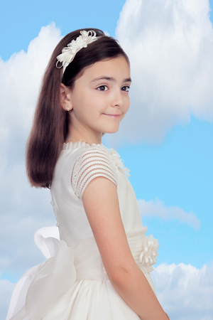 Adorable little girl dressed in communion with a blue sky of background photo