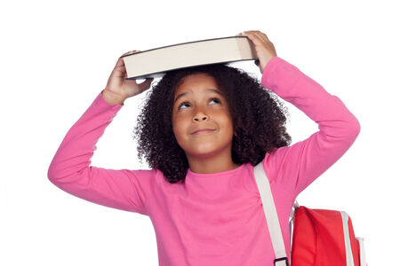 Little student girl with a book on her head isolated on a white background photo