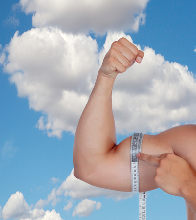 Muscular arm of a mans biceps measure yourself against a blue sky photo