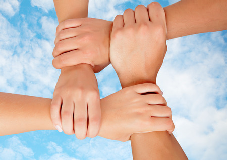 hands joined: Joined hands in a symbol of cooperation on a sky with clouds