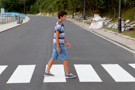 road safety: Teenager through a zebra crossing in his town