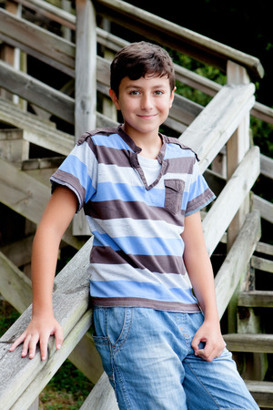Nice preteen boy smiling with a striped shirt in wooden stairs photo