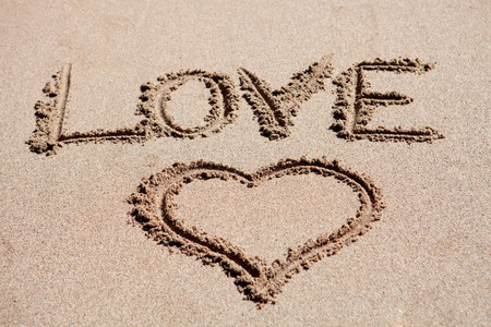 Love holiday. Painted heart on beach sand photo