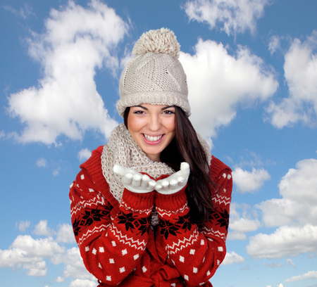 Attractive young caucasian woman in warm clothing with a blue sky of background photo