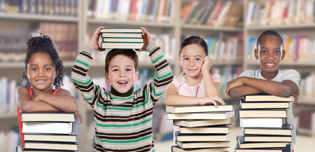 Four children in the library with many books Foto de archivo