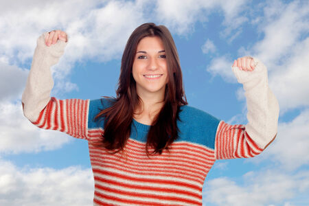 Casual girl celebrating something with a blue sky of background photo