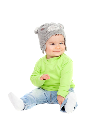 0 6 months: Beautiful baby  with wool hat sitting on the floor isolated
