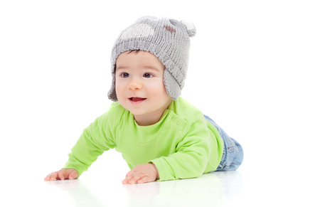0 6 months: Beautiful baby  with wool hat lying on the floor isolated