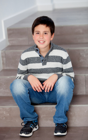 preteen: Preteen boy sitting on the stairs at home Stock Photo