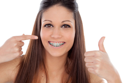 Attractive young woman with brackets saying Ok isolated on a white backgroung