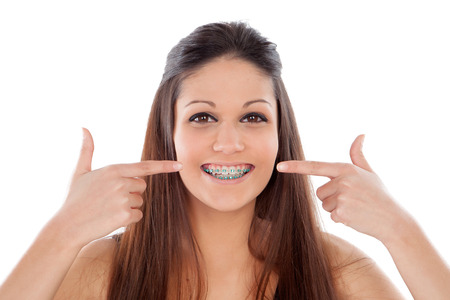 dental: Attractive young woman pointing her brackets isolated on a white backgroung Stock Photo