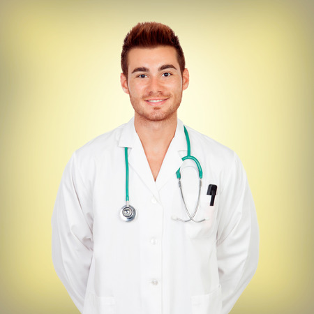 sympathetic: Sympathetic young doctor with a yellow background Stock Photo