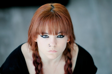 Rebellious teenager girl with red hair very angry view from above